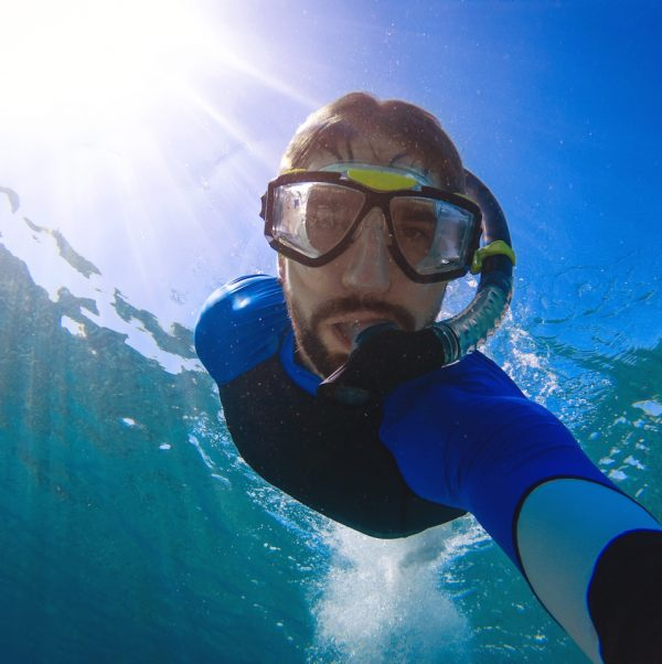 Young man takes underwater selfie.